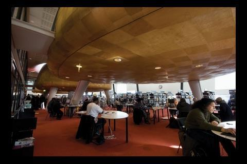 Students at internet-linked tables below the pods are not disturbed by traditional library users perusing the bookshelves